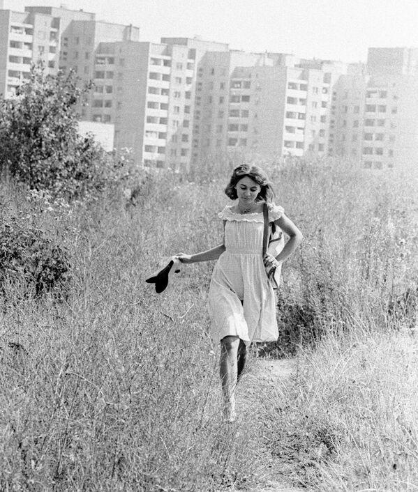 Девушка бежит по тропинке в поле, расположенном рядом с новостройкой, Минск, 1985 год. - Sputnik Беларусь