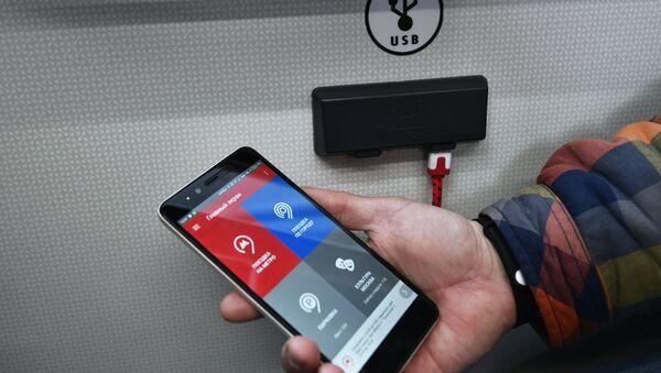 Пассажир заряжает телефон от розетки - Sputnik Беларусь