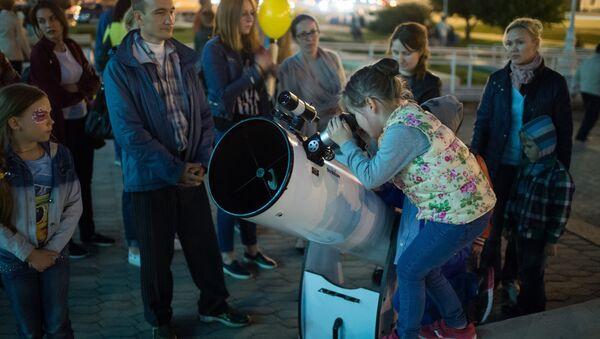 Дзяўчынка глядзіць у тэлескоп, архіўнае фота - Sputnik Беларусь