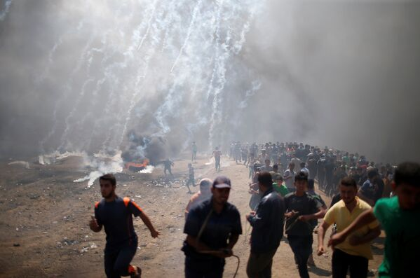 Палестинские демонстранты бегут от слезоточивого газа, распыленного израильскими войсками - Sputnik Беларусь