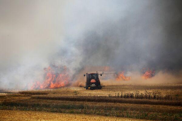 Трактор кибуца Мефальсима в горящем поле недалеко границы между Израилем и Газой - Sputnik Беларусь