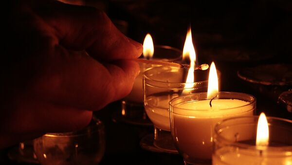 Человек зажигает свечи - Sputnik Беларусь