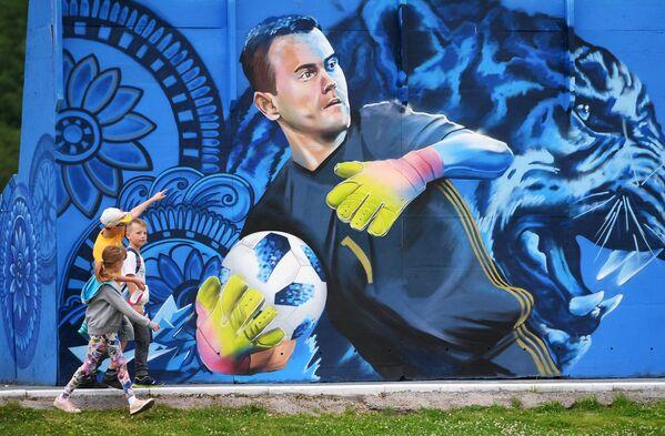 Дети рассматривают граффити с изображением вратаря сборной России по футболу Игоря Акинфеева в Щелково - Sputnik Беларусь