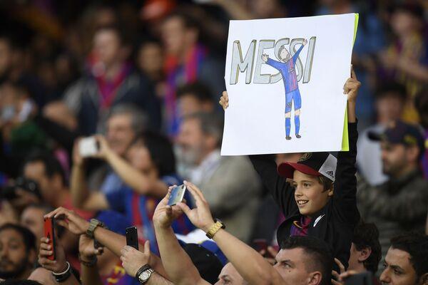 Юный болельщик с плакатом с изображением форварда Барселоны Лионеля Месси перед матчем между Барселоной и Реал Мадридом в Барселоне. - Sputnik Беларусь