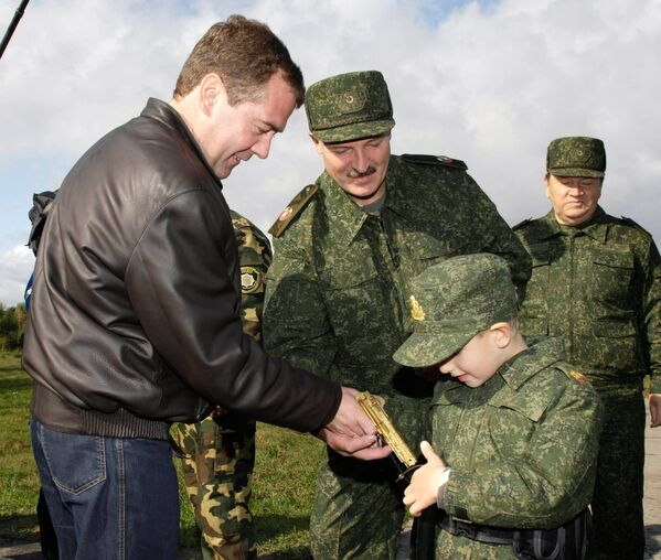 А вот и собственный пистолет. И не простой, а золотой! Президент России Дмитрий Медведев вручает подарок Коле во время учений на полигоне Обуз-Лесновский в Брестской области. - Sputnik Беларусь