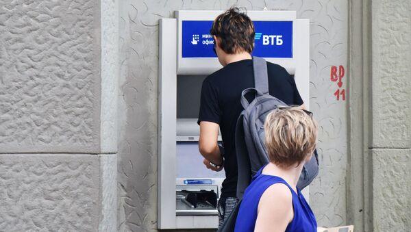 Мужчина снимает деньги в банкомате ВТБ. - Sputnik Беларусь