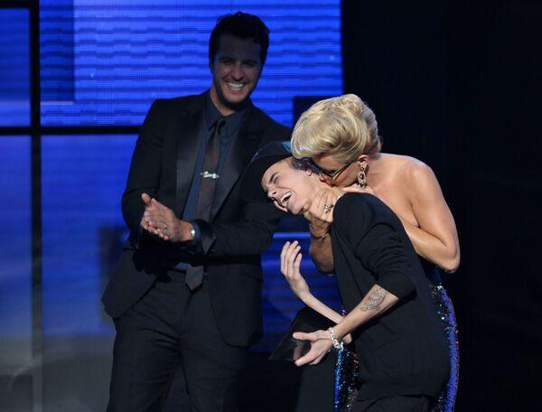 Бибер принимает награду и поцелуи ведущей Дженни Маккарти за альбом Believe на American Music Awards в 2012 году. - Sputnik Беларусь