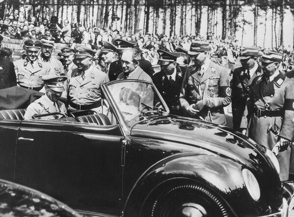 Рейхсканцлер Германии Адольф Гитлер осматривает первый Volkswagen Жук, построенный в Штутгарте в 1937 году. Однако массовому производству во многом революционной машины помешала война. - Sputnik Беларусь