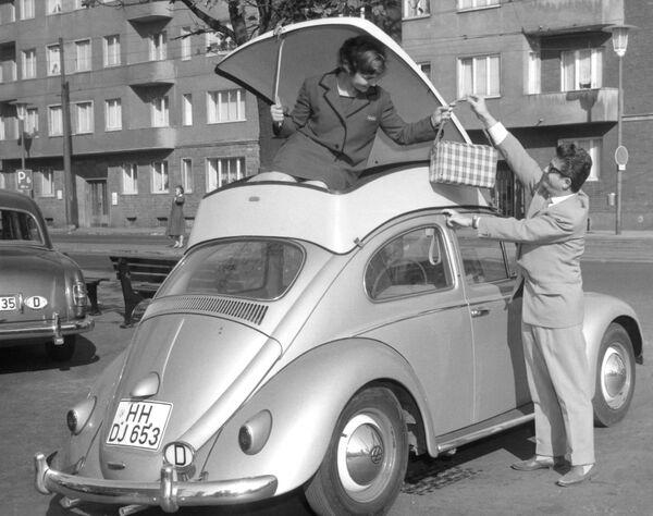 Девушка демонстрирует пластиковый контейнер, прикрепленный к крыше автомобиля Volkswagen Beetle – дополнительное место для багажа. Его представили на Международной выставке пластмасс в Дюссельдорфе, Германия, в 1959 году. - Sputnik Беларусь