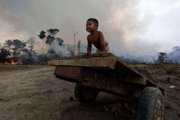 Ребенок играет во время природного пожара в лесах Амазонии  - Sputnik Беларусь