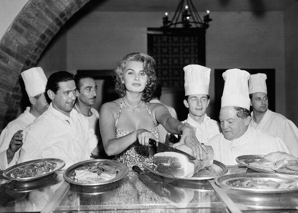 Софи Лорен – прекрасная хозяйка и автор книги рецептов. На этом фото она выскользнула с большой вечеринки в отеле Эксельсиор в Венеции 25 августа 1955 года, чтобы нарезать ветчину на тонкие пластинки. Ее поклонники-повара в восторге. - Sputnik Беларусь