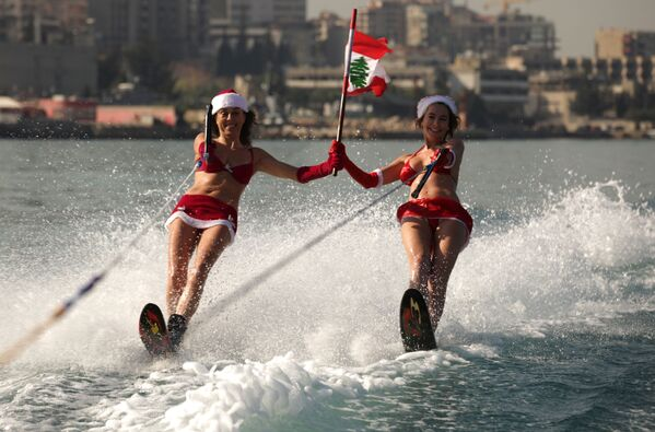 Ліванскія дзяўчыны ў касцюмах Санта-Клаўса на водных лыжах падчас шоу ў бухце Джуніі, у 20 км на поўнач ад Бейрута. - Sputnik Беларусь