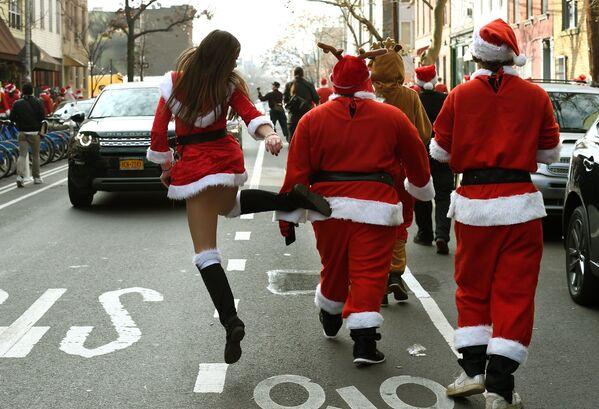 Санта-Клаўсы ідуць на парад у парку ў Брукліне падчас SantaCon у Нью-Йорку. - Sputnik Беларусь