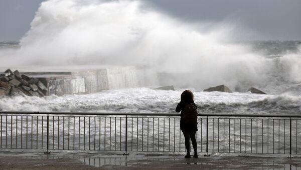 Женщина смотрит на волны во время шторма Глория на пляже в Барселоне - Sputnik Беларусь