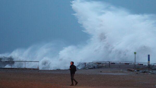 Мужчина во время шторма Глория на пляже в Испании - Sputnik Беларусь