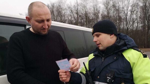 Инспектор вручает водителю листовку - Sputnik Беларусь