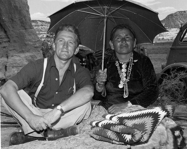 Кирк Дуглас и коренная индианка прячутся от палящего солнца, наблюдая за съемкой сцены фильма Туз в рукаве (1950) в Нью-Мексико. В картине актер исполнил сложную роль беспринципного журналиста. - Sputnik Беларусь
