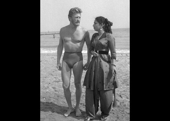 Киноактер Кирк Дуглас и индийская актриса Мехтаб отдыхают на пляже Лидо 1 сентября 1953 года во время Венецианского кинофестиваля.  - Sputnik Беларусь
