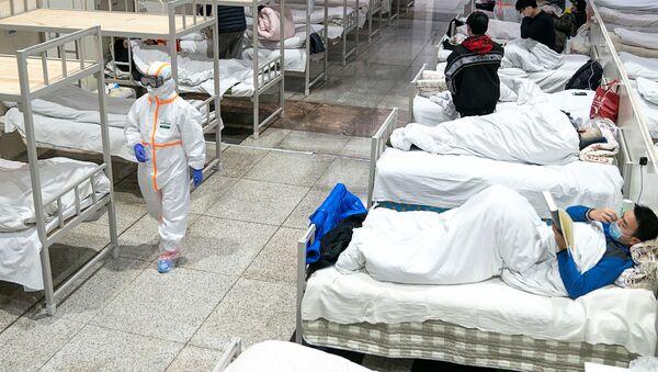 Медыцынскія работнікі ў ахоўных касцюмах абслугоўваюць пацыентаў у Міжнародным выставачным цэнтры Ухань - Sputnik Беларусь