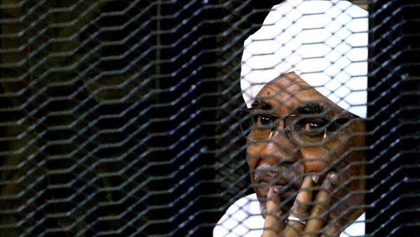 Бывший президент Судана Омар Хасан аль-Башир сидит в клетке в здании суда  - Sputnik Беларусь