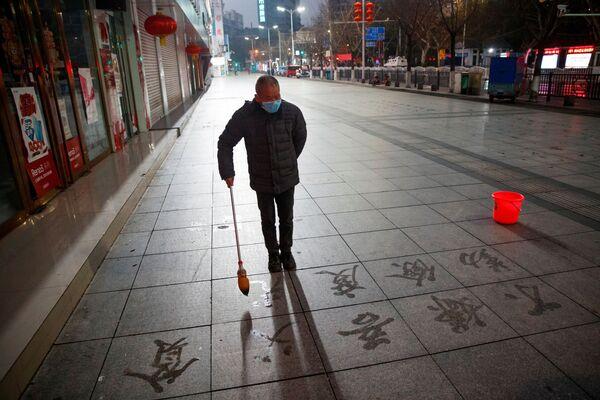 Человек практикует каллиграфию на асфальте на безлюдной улице в Цзюцзяне - Sputnik Беларусь