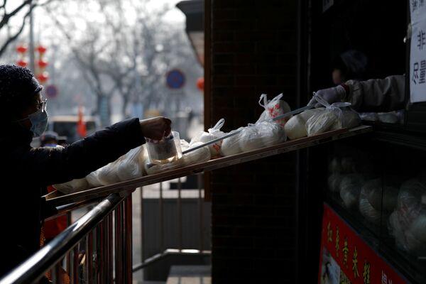Покупатель в маске платит за булочки через контейнер на палочке - Sputnik Беларусь