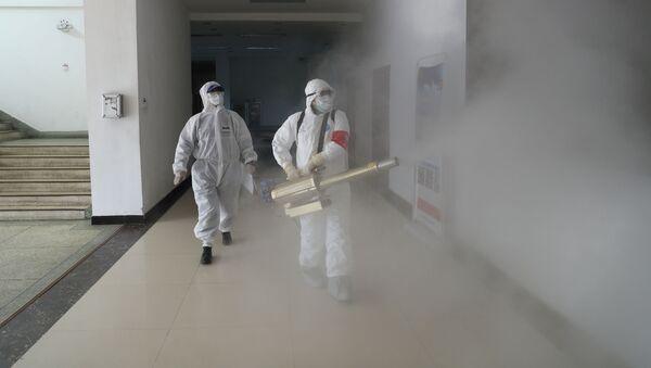 Волонтеры в защитных костюмах дезинфицируют жилой комплекс в Ухани - Sputnik Беларусь