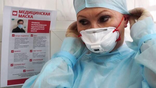Сотрудница Центра гигиены и эпидемиологии надевает защитную медицинскую маску  - Sputnik Беларусь