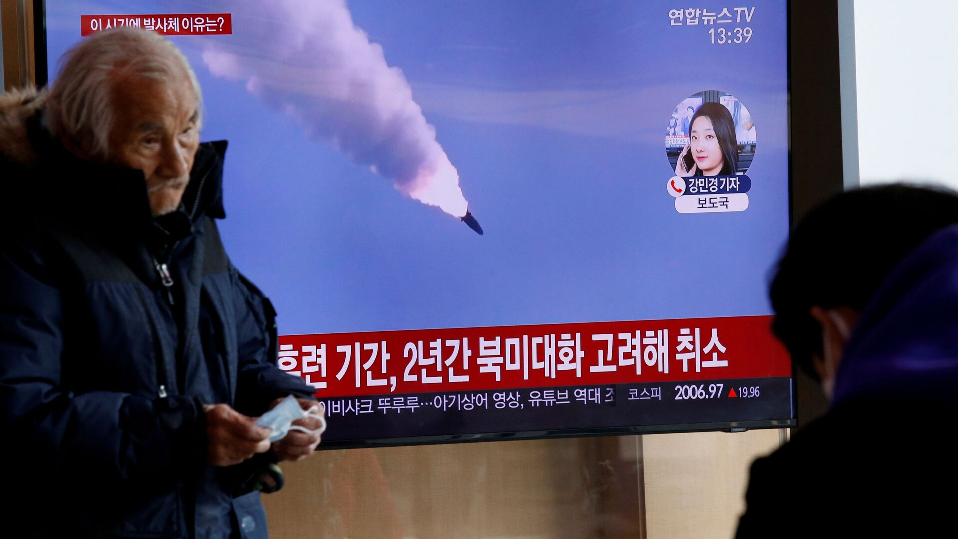 Мужчина проходит мимо телевизора, демонстрирующего полет северокорейских ракет - Sputnik Беларусь, 1920, 28.09.2021