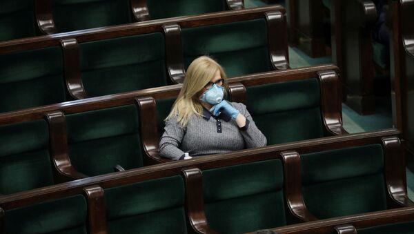 Во время заседания у здания парламента член парламента носит защитную маску, поскольку в Варшаве продолжается распространение коронавирусной болезни (COVID-19) - Sputnik Беларусь