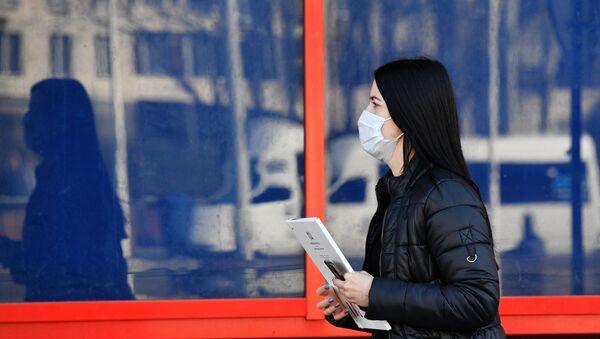 Жительница Минска идет по улице в защитной маске - Sputnik Беларусь