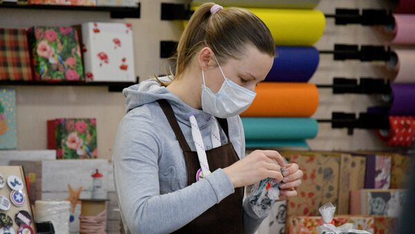Девушка в защитной маске упаковывает подарки в торговом центре Дана Молл в Минске - Sputnik Беларусь