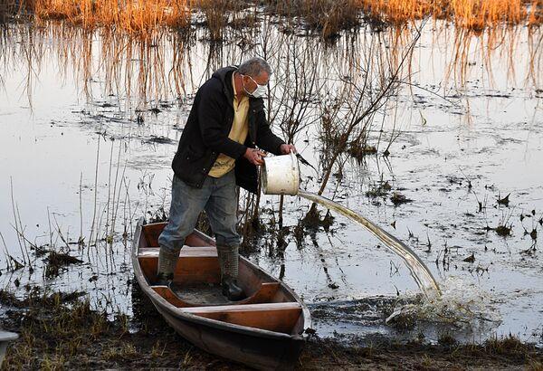 Паляшук вычэрпвае ваду з лодкі каля заліва Прыпяці. - Sputnik Беларусь
