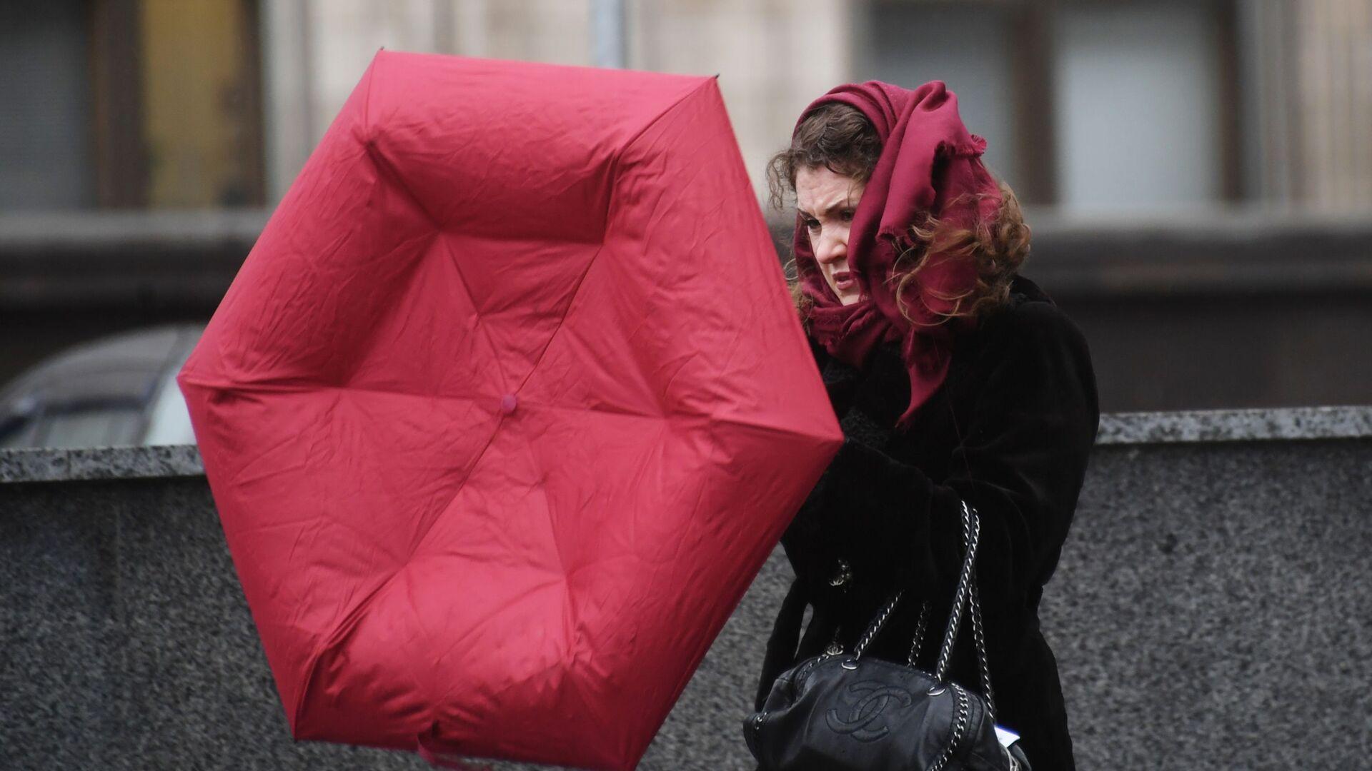 Девушка с зонтом идет по улице под порывами ветра - Sputnik Беларусь, 1920, 14.10.2021