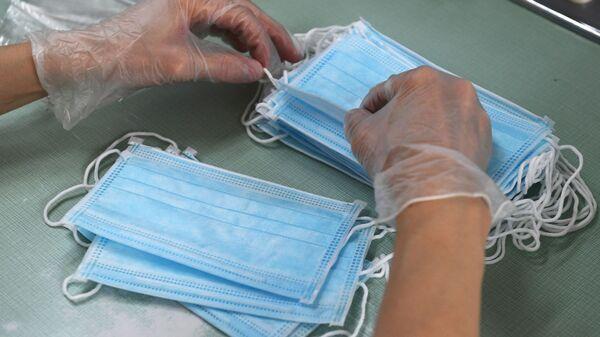 Сотрудница аптеки фасует одноразовые медицинские маски в упаковки - Sputnik Беларусь