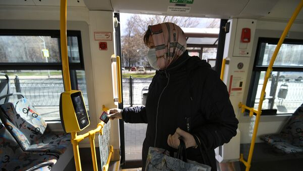 Женщина в защитной маске в салоне городского автобуса - Sputnik Беларусь