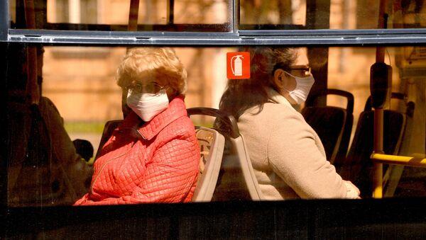 Женщины в защитных масках едут в общественном транспорте - Sputnik Беларусь