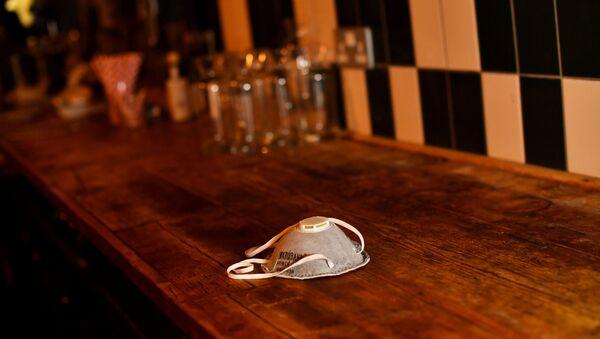 Маска на барной стойке в одном из заведений Лондона - Sputnik Беларусь