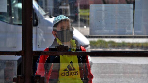 Мальчик в защитной маске на остановке транспорта в Минске - Sputnik Беларусь