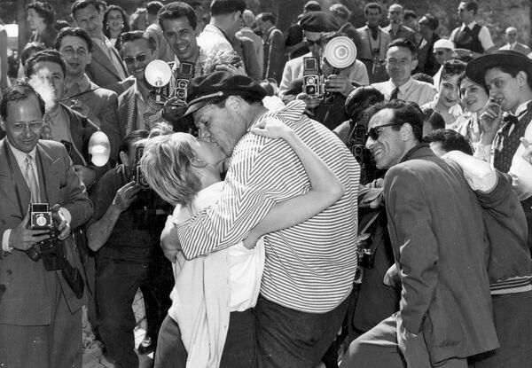 Один из незабываемых моментов, которые подарил  Каннский кинофестиваль за всю свою историю: 28 апреля 1955 года французский актер и певец Эдди Константин целует свою новую подругу Элен Мюссель перед окружившими их фотографами. - Sputnik Беларусь