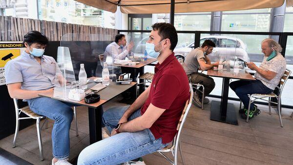 Люди в защитных масках сидят на террасе ресторана в Милане, Италия - Sputnik Беларусь