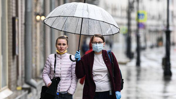 Женщины под зонтом на улице города - Sputnik Беларусь