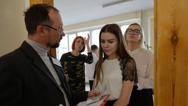 Выкладчык звярае асобу па пашпарце перад пачаткам экзамену - Sputnik Беларусь