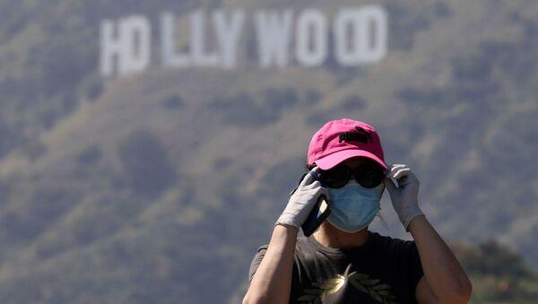 Человек в маске не фоне надписи Hollywood  - Sputnik Беларусь