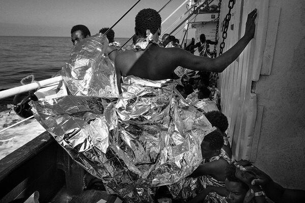 Спасенные мигранты в термоодеялах на борту Маре Джонио из серии итальянского фотографа Франческо Беллина - Sputnik Беларусь