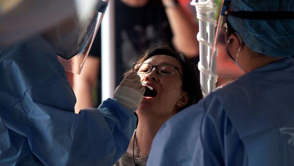 Медицинский работник в защитном костюме берет мазок у женщины на открытой площадке во время массового тестирования на коронавирус COVID-19 в Пекине 23 июня 2020 года. - Sputnik Беларусь